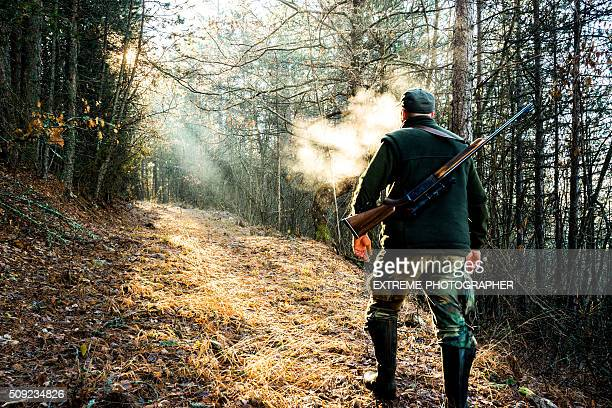 hunter with rifle walking in the forest - hunting sport stock pictures, royalty-free photos & images