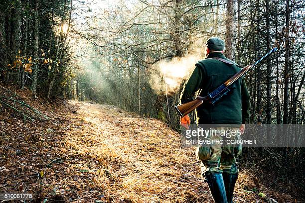 Hunter with rifle walking in the woods