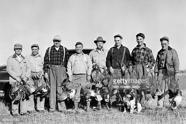 Hunters and their pheasants pose together ca 1950