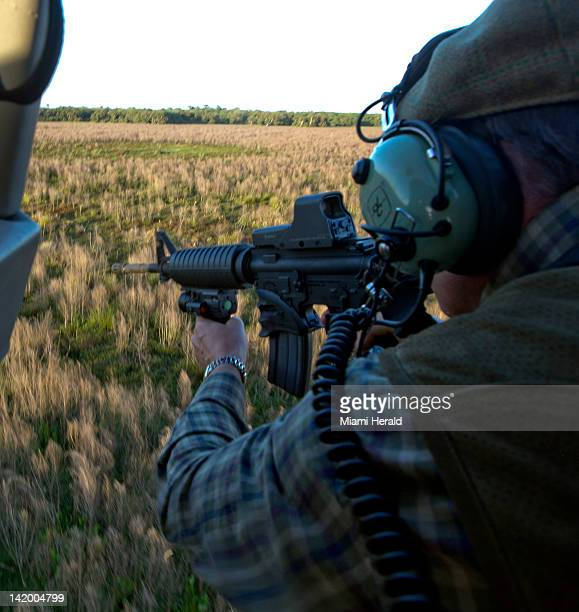 Hunters fly by helicopter and chase down wild hogs on a ranch in Okeechobee Florida March 13 2012 Here hunter Chris Mayberry from New York takes aim...