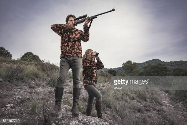 hunters man with rifle and woman with binoculars in spain - shotgun stock pictures, royalty-free photos & images