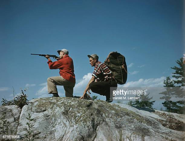 hunters on rock aiming rifle  - number of people stock pictures, royalty-free photos & images
