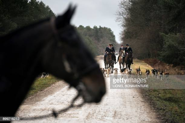 Hunters ride their horse during a hunting with hounds on December 23 2017 in the forest near Chatenoy center France Since a month hunting enthusiasts...