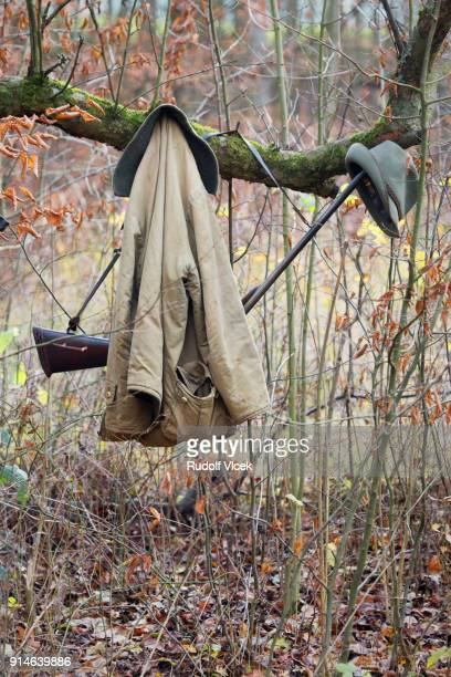 hunting equipment, rifles (weapons), coats hanging on a tree branch in forest - czech hunters stock-fotos und bilder