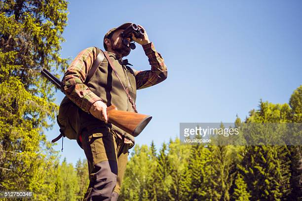 Hunting Man Observing The Field Through Field Glasses
