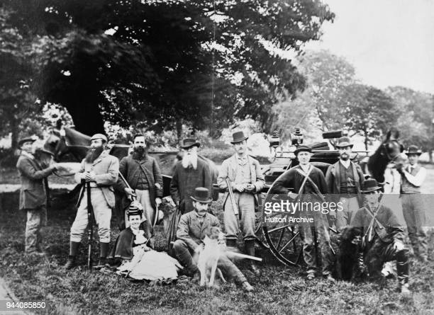A hunting party posing in front of a shooting brake 1869