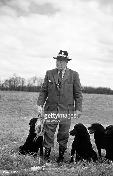 Portrait of John Olin posing with dogs while holding pheasant during hunting expedition photo shoot at Olin Kennels at Nilo Farms Olin who serves as...