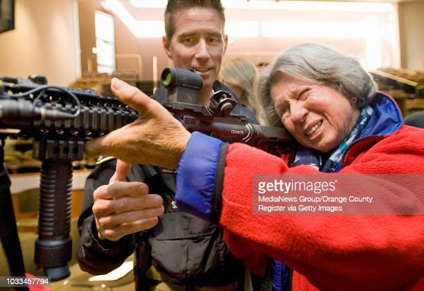 Huntington Beach Librarian Rebecca Indyk looks through the scope of officer Steve Fong's AR15 rifle during a seminar on workplace violence City...