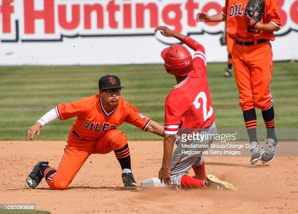 Huntington Beach's Cole Minato tags out Los Alamitos' AJ Mayeda as he tries to steal second base during their Sunset League game in Hermosa Beach on...