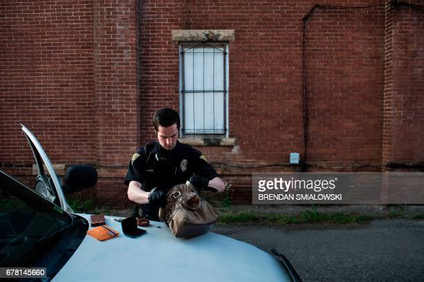 Huntington Police Officer Alex Marshall searches the purse of a suspected prostitute on April 19 2017 in Huntington West Virginia Marshall found...
