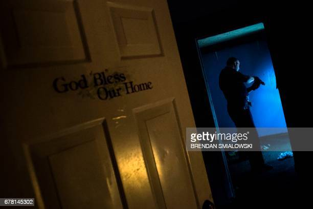 Huntington Police Officer Dakota Dishman searches an abandoned house littered with needles and known for drug use on April 19, 2017 in Huntington,...