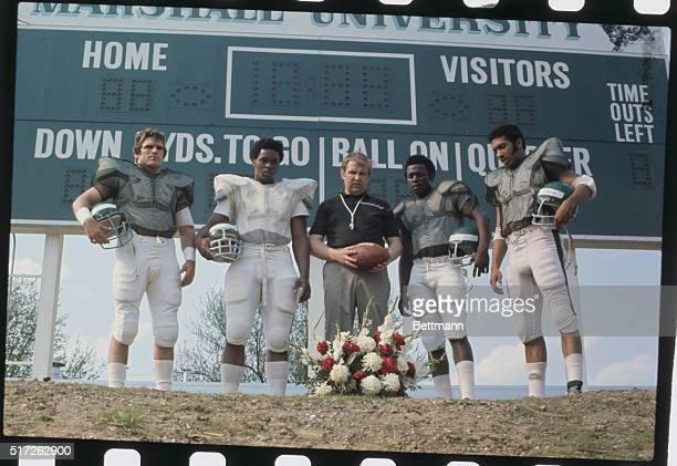 Huntington, West Virginia: The four remaining starters from the 1970 first string team of Marshall University take time out to pause at flower...