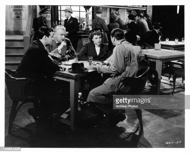 GP Huntley and Nigel Bruce watch Laraine Day preparing to leave Robert Young wearing a pith helmet in a scene from the film 'Journey For Margaret'...