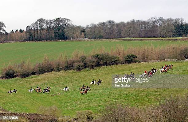Huntsmen riding across fields during the Heythrop New Year's Day Hunt Oxfordshire