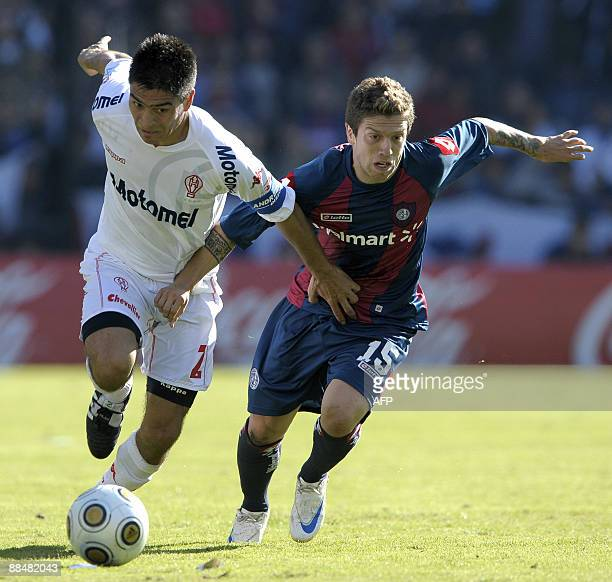 Huracan's footballer Paolo Goltz vies for the ball with Alejandro Gomez of San Lorenzo during their Argentina first division football match in Buenos...