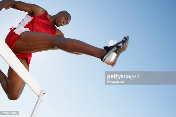 hurdler jumping - athletics stock photos and pictures