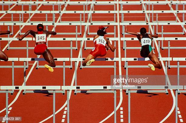 hurdles, female athletes in action, rear view - hurdling track event stock pictures, royalty-free photos & images