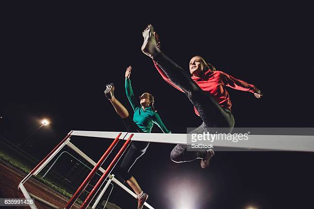 hurdling young athletes - athletics stock photos and pictures