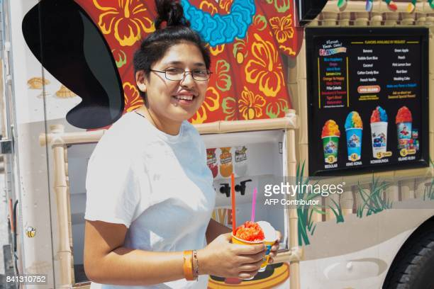 Hurricane Harvey evacuee Jasmine enjoys shaved ice at the Delco Center in east Austin Texas on Thursday August 31 2017 A Kona Ice truck visited the...