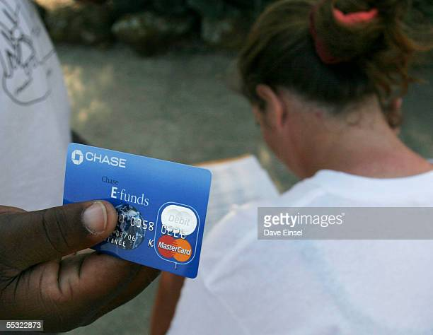 Hurricane Katrina evacuee displays his FEMA debit card as his partner reads over the directions for its use outside Reliant Arena, near the Astrodome...