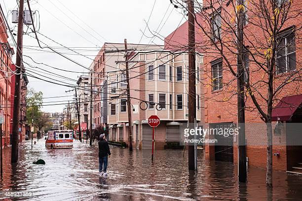 hurricane sandy: man standing on a flooded street - new jersey bildbanksfoton och bilder