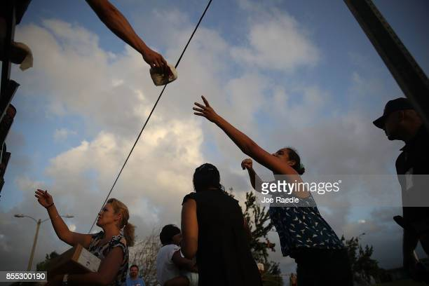 Hurricane survivors receive food and water being given out by volunteers and municipal police as they deal with the aftermath of Hurricane Maria on...