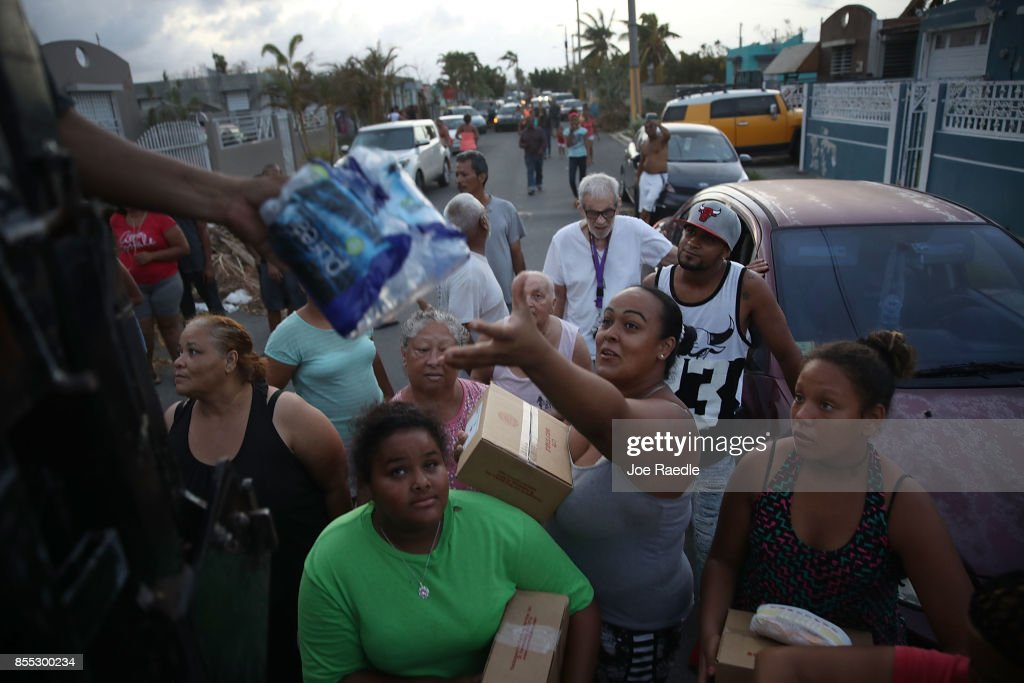 Hurricane survivors receive food and water being given out by volunteers and municipal police as they deal with the aftermath of Hurricane Maria on September 28, 2017 in Toa Baja, Puerto Rico. Puerto Rico experienced widespread damage including most of the electrical, gas and water grid as well as agriculture after Hurricane Maria, a category 4 hurricane, passed through.