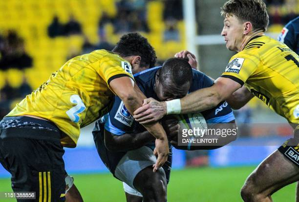 Hurricanes' Isaia Walker-Leawere and Beauden Barrett try to stop Bulls Trevor Nyakane during the Super Rugby match between New Zealand's Hurricanes...