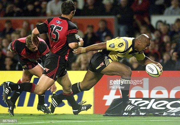 Hurricanes Jonah Lomu runs in to score his try despite the tackle of Crusaders Justin Marshall in their Super 12 rugby match played at Jade Stadium...