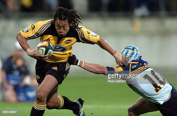 Hurricanes Tana Umaga hands off Brumbies Matt Giteau on the way to the tryline in the Super 12 rugby at Westpac Stadium Wellington New Zealand...