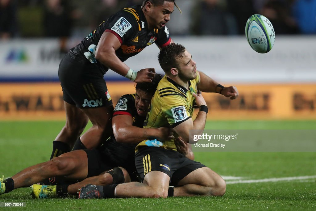 Hurricanes' Wes Goosen (C) is tackled by Chiefs Johnny FaÕauli (top), who was red carrded for this tackle and Anton Lienert-Brown during the round 19 Super Rugby match between the Chiefs and the Hurricanes at Waikato Stadium on July 13, 2018 in Hamilton, New Zealand.