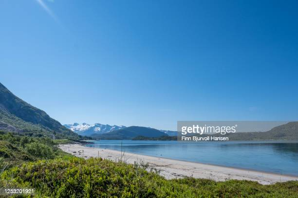 hurtigruten travelling north in norway, photographed from a beach in northern norway - finn bjurvoll stock pictures, royalty-free photos & images