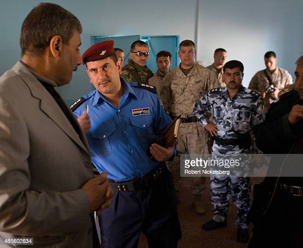 Husayba's mayor Farhan T. Farhan, left, speaks with a local city police official as other Iraqi Army and U.S. Marine officers wait for their weekly...