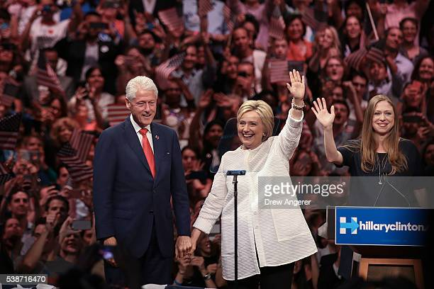 Husband and former president Bill Clinton Democratic presidential candidate Hillary Clinton and daughter Chelsea Clinton acknowledge the crowd during...