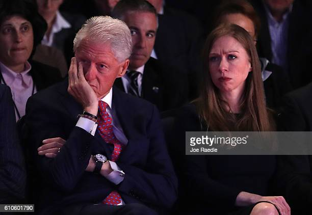 Husband and former US President Bill Clinton and daughter Chelsea Clinton listen as Democratic presidential nominee Hillary Clinton speaks during the...