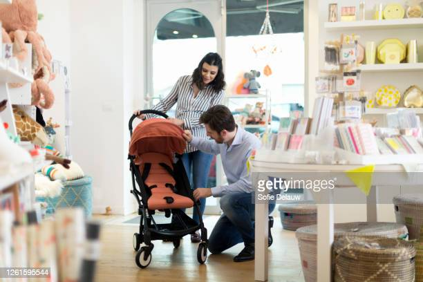 husband and pregnant wife shopping for pram - carriage stock pictures, royalty-free photos & images