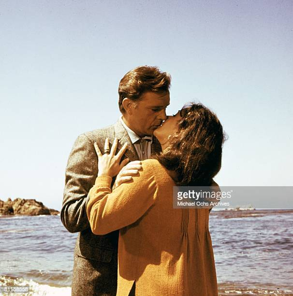 Husband and wife actors Elizabeth Taylor and Richard Burton kiss in a scene from the movie 'The Sandpiper' which was released on June 23 1965