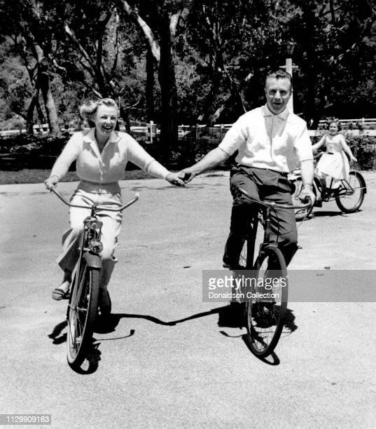 Husband and wife actors June Allyson and Dick Powell ride bikes holding hands with their daughter Pamela Allyson Powell trailing them at home in 1954