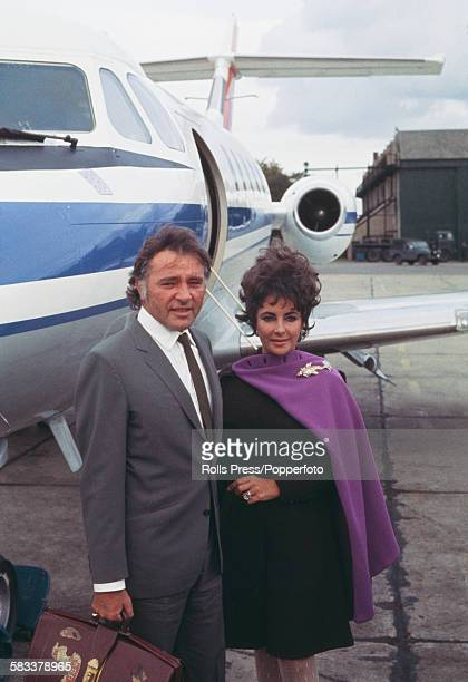Husband and wife actors Richard Burton and Elizabeth Taylor pose together in front of their twin engined private jet at RAF Abingdon airport in...