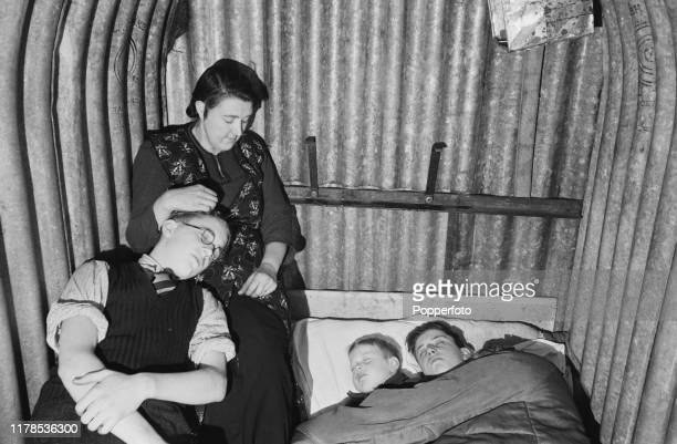A husband and wife and their two sons attempt to sleep in an Anderson air raid shelter made from galvanised corrugated steel panels at their home in...