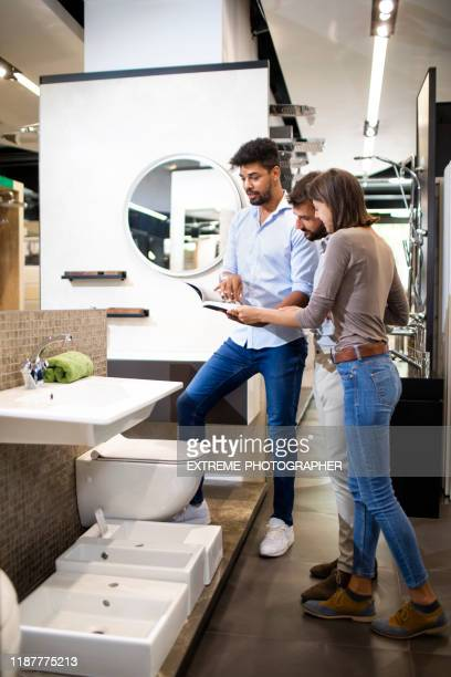 a husband and wife being helped by a store seller in finding a right bathroom sink for their home in a specialized store - casal chuveiro imagens e fotografias de stock