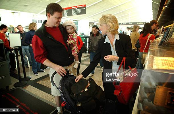 Husband and wife Cole Kimball and Laura Love and their daughter Kirby all head for their flights at DIA Laura with brief case in hand is on a busines...