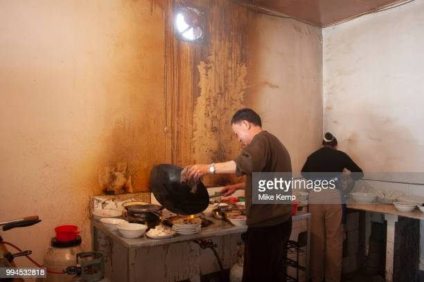 Husband and wife cook pork and vegetable dishes at a small restaurant in Zhongdian, Yunnan province, China. The man puts various dishes together at...