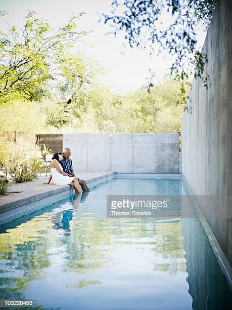 husband and wife couple embracing on edge of pool - emotional support stock pictures, royalty-free photos & images
