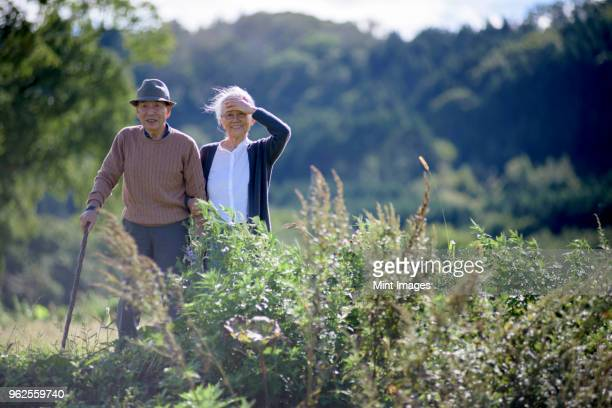 Husband and wife, elderly man wearing hat and using walking stick and elderly woman walking along path.