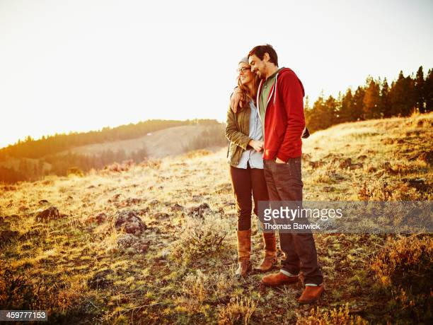 Husband and wife embracing and watching sunset