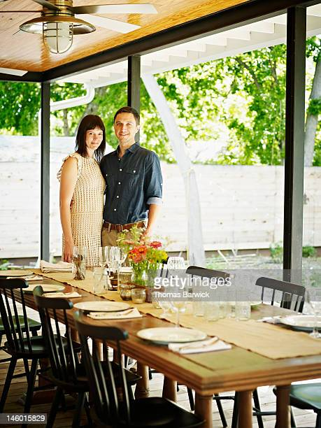 Husband and wife embracing behind table on porch