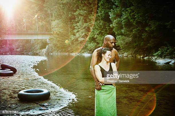 Husband and wife embracing by river after swimming