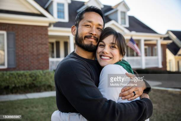 husband and wife embracing in front of home - 35 39 years stock pictures, royalty-free photos & images