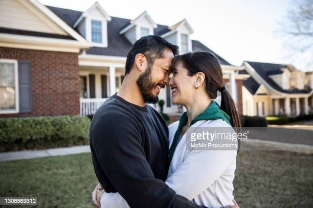 husband and wife embracing in front of home - mortgage stock pictures, royalty-free photos & images